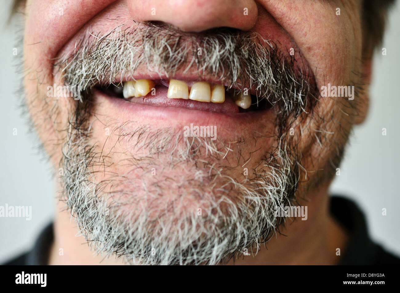 part of a man's face with a smiling toothless - Stock Image