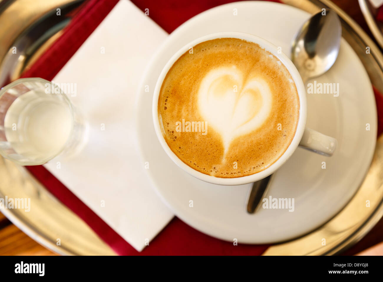 Coffee espresso with coffee art decorated heart in froth - Stock Image