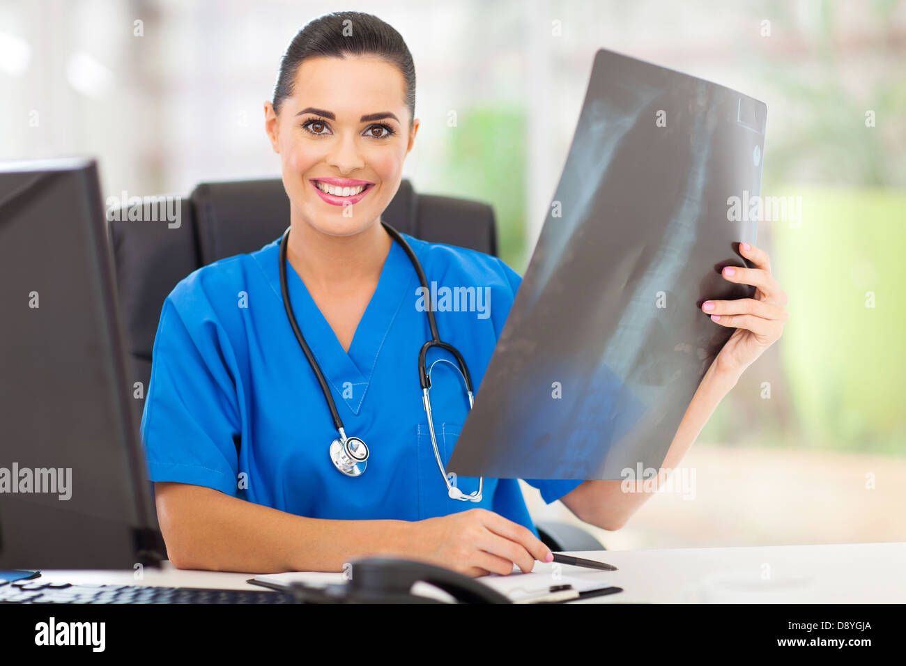 female medical doctor with a an x-ray in hospital office - Stock Image