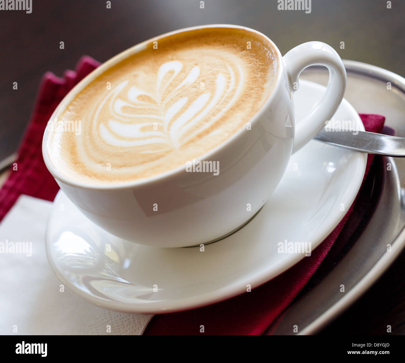 Coffee late with coffee art with a decorated tree in froth - Stock Image