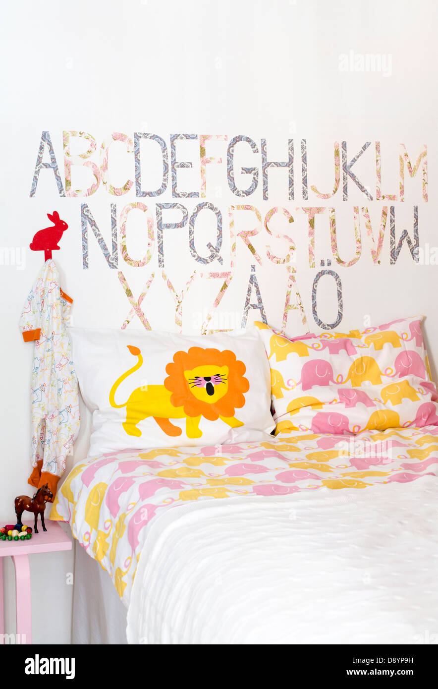 Nursery room with bed and alphabets on wall - Stock Image