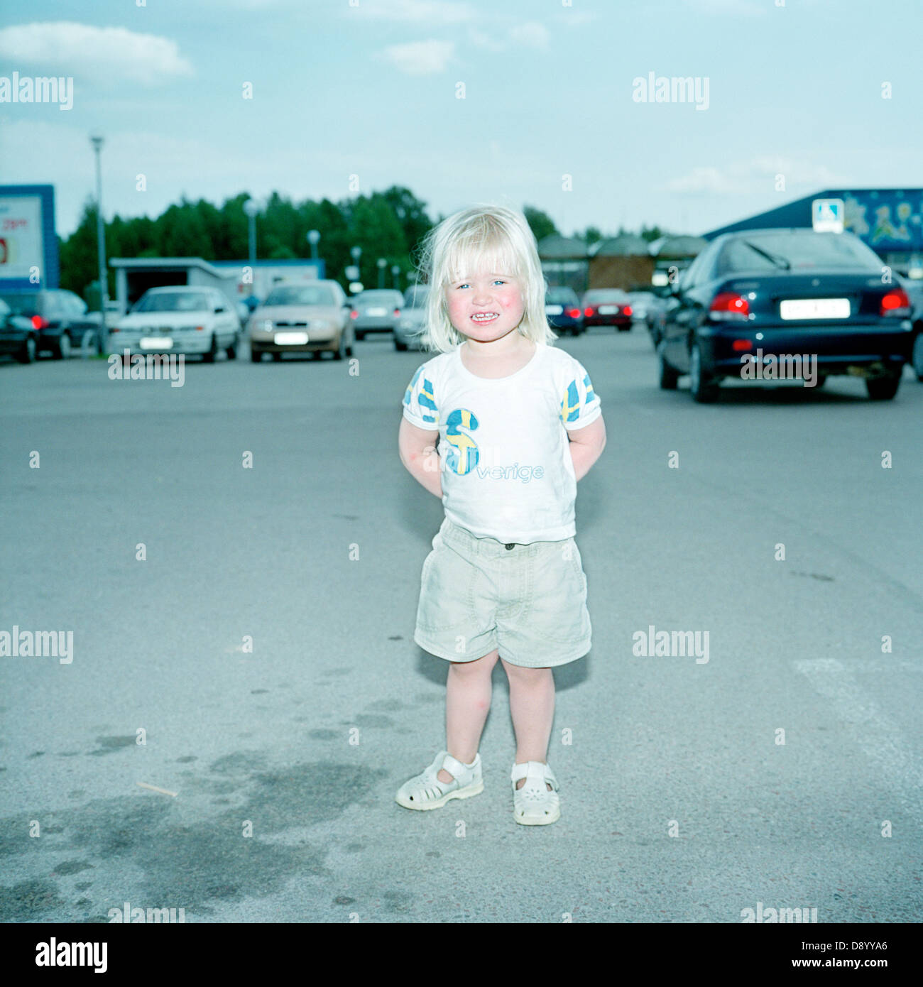 A smiling little girl standing in a parking lot, Sweden. - Stock Image
