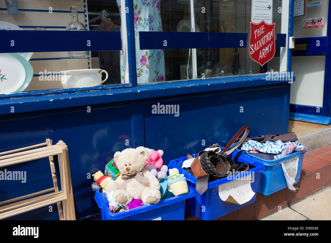 A teddy bear and other items for sale in boxes outside a Salvation Army charity shop. - Stock Image