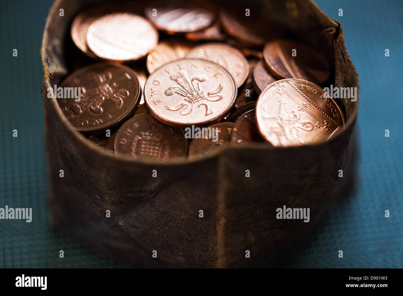 Small leather pouch full of two pence coins, London, England, UK - Stock Image