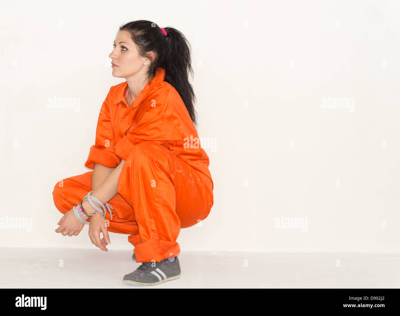 Woman in bright orange overalls squatting down facing left watching something off frame - Stock Image