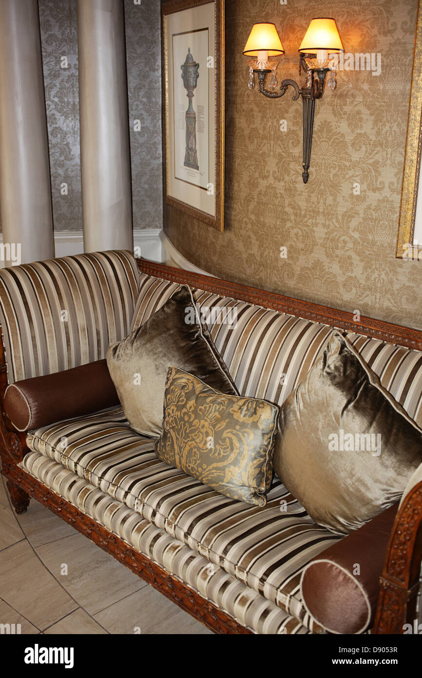 Upholstered chair with accenting cushions - Stock Image