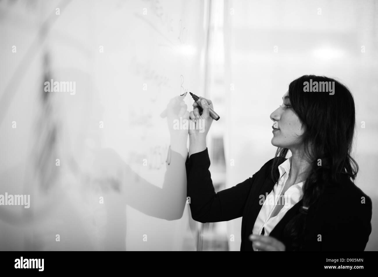 Woman writing on white board - Stock Image
