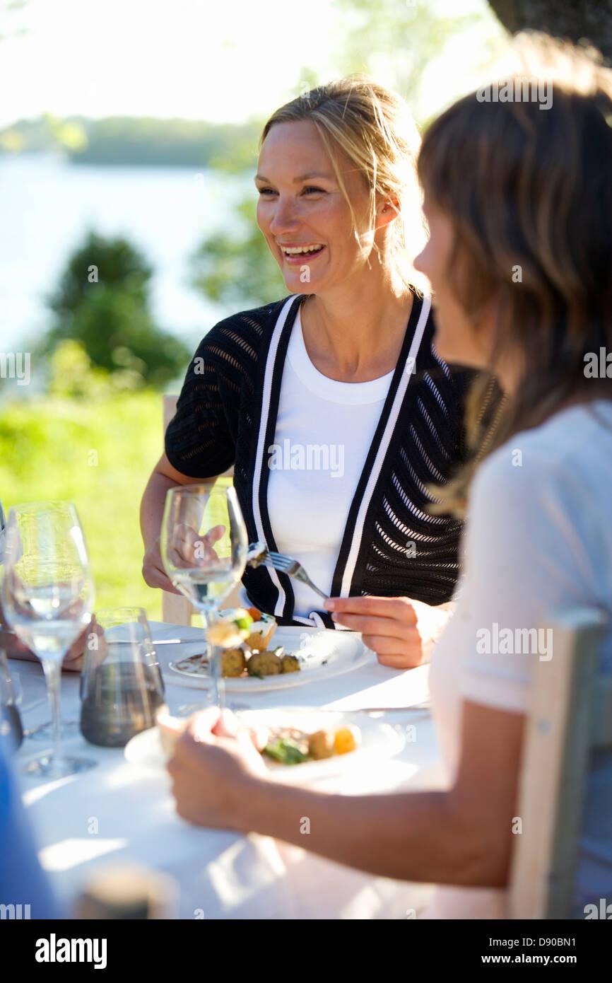 Two women having lunch at a midsummer party, Fejan, Stockholm archipelago, Sweden. Stock Photo