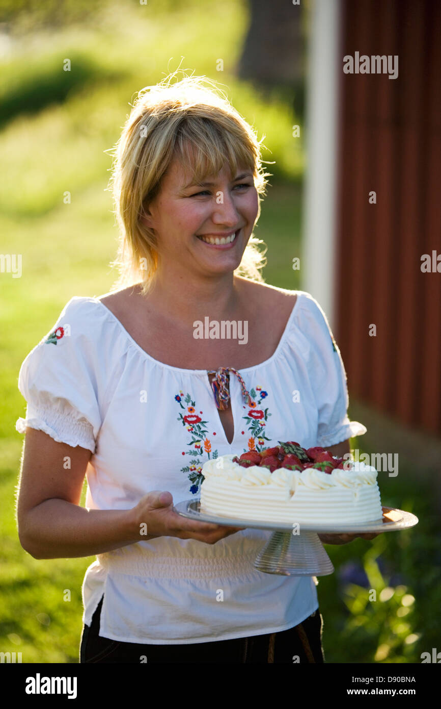 A woman and a strawberry cake, Fejan, Stockholm archipelago, Sweden. Stock Photo