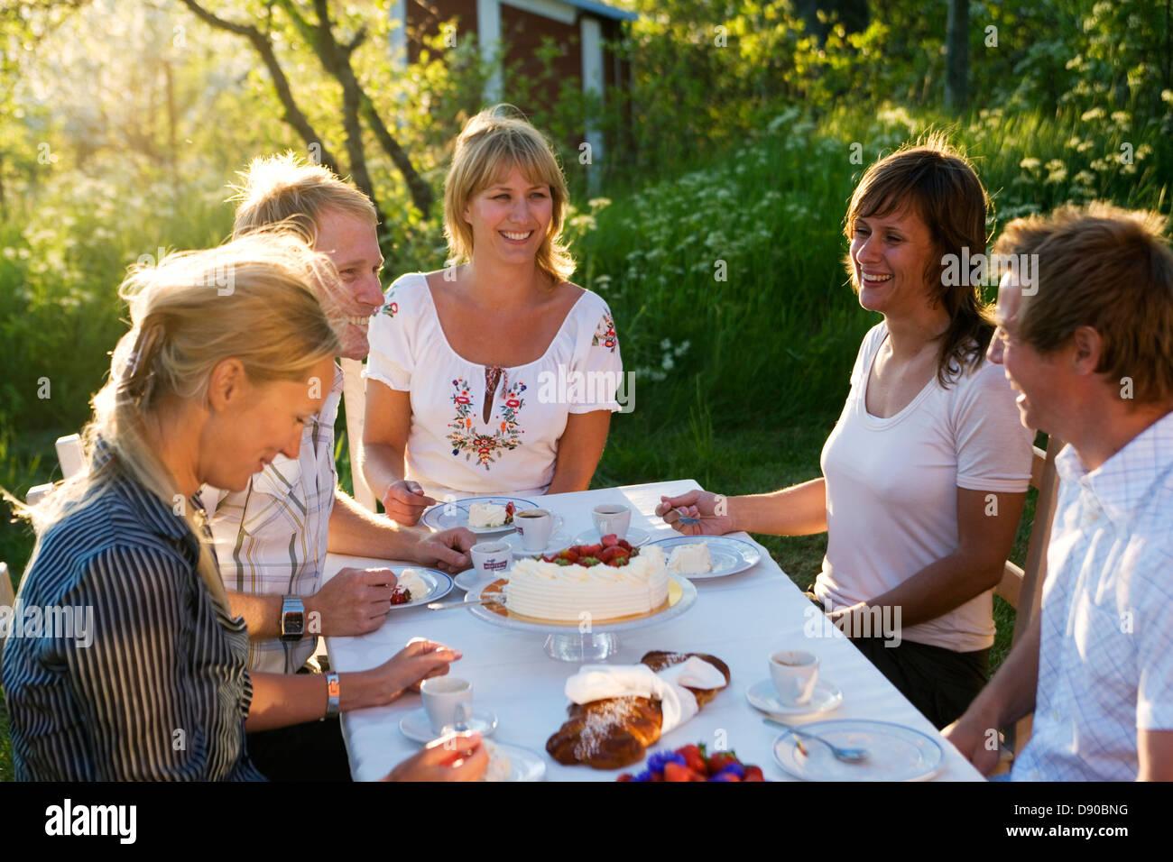 Five friends having a cake during midsummer, Stockholm archipelago, Sweden. Stock Photo
