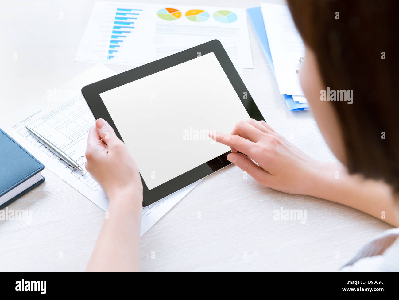 Caucasian businesswoman sitting at workplace and looking on blank modern digital tablet, touching on empty screen - Stock Image