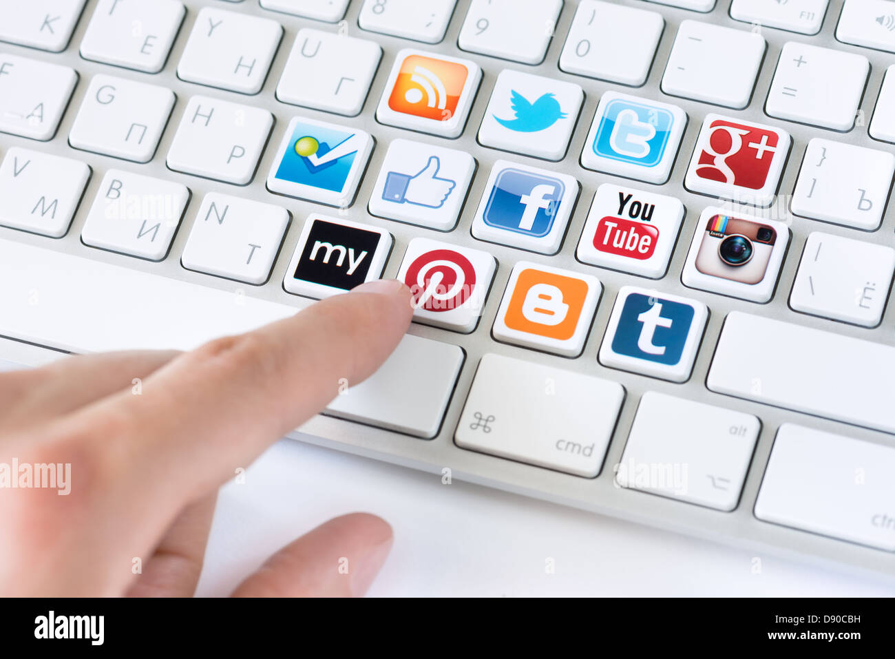 Hand pointing on keyboard with social media logotype collection of well-known social network brand's placed - Stock Image