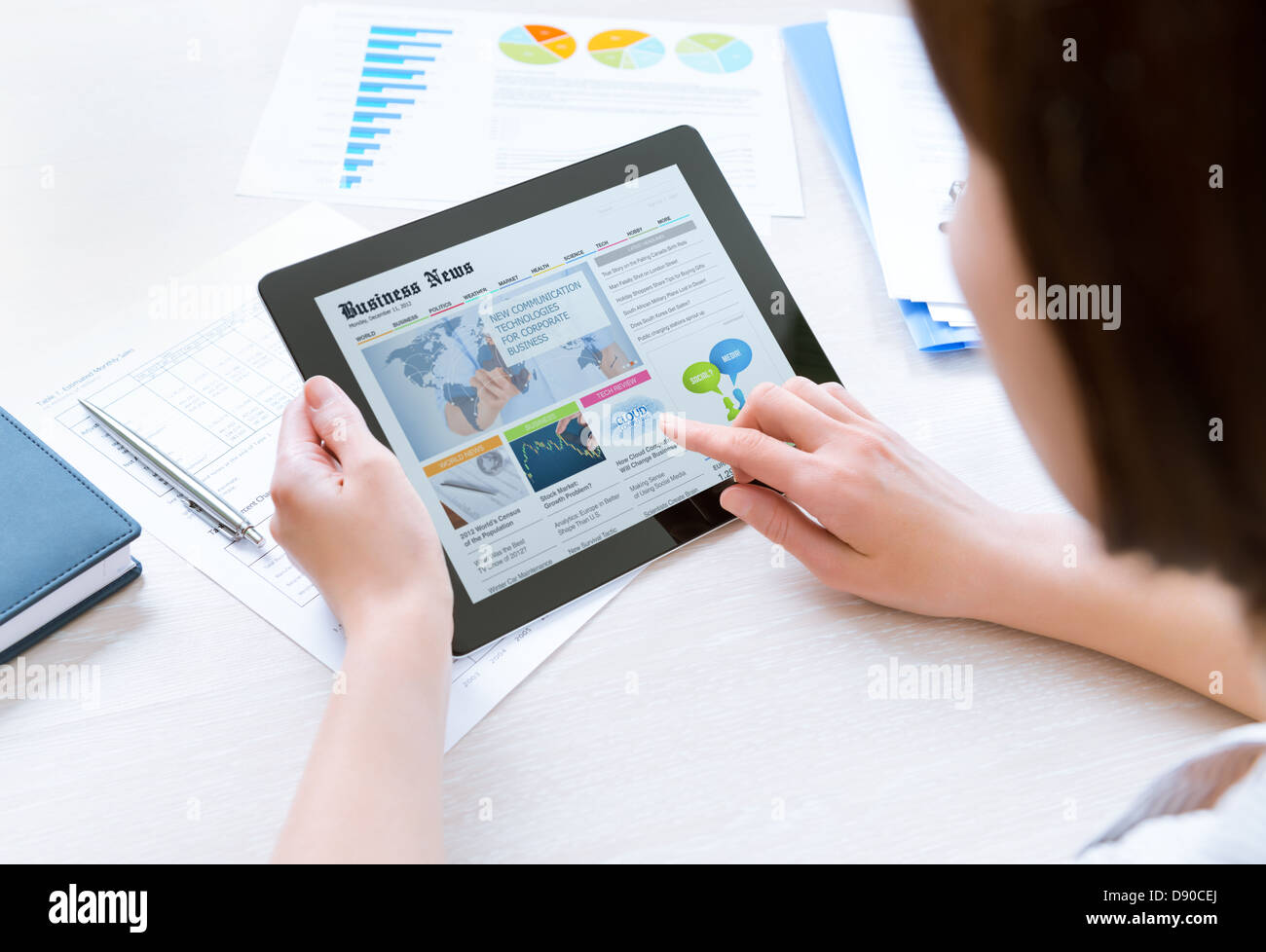 Businesswoman wearing casual shirt sitting at desk and looking latest business news on digital tablet in the office - Stock Image