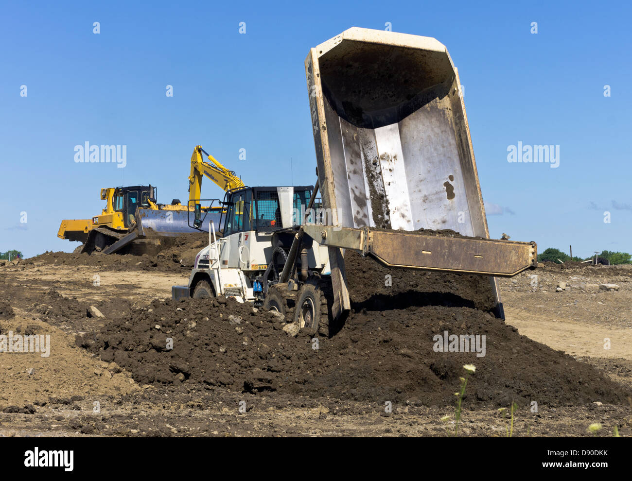 Dump Truck Unloading Earth On Construction Site