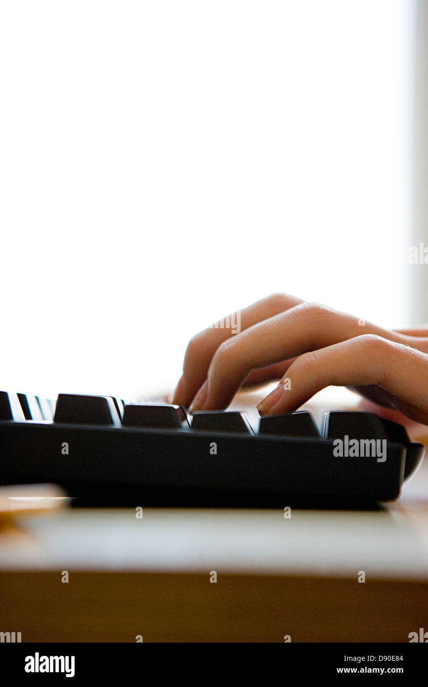 A womans hand on a computer keyword. - Stock Image