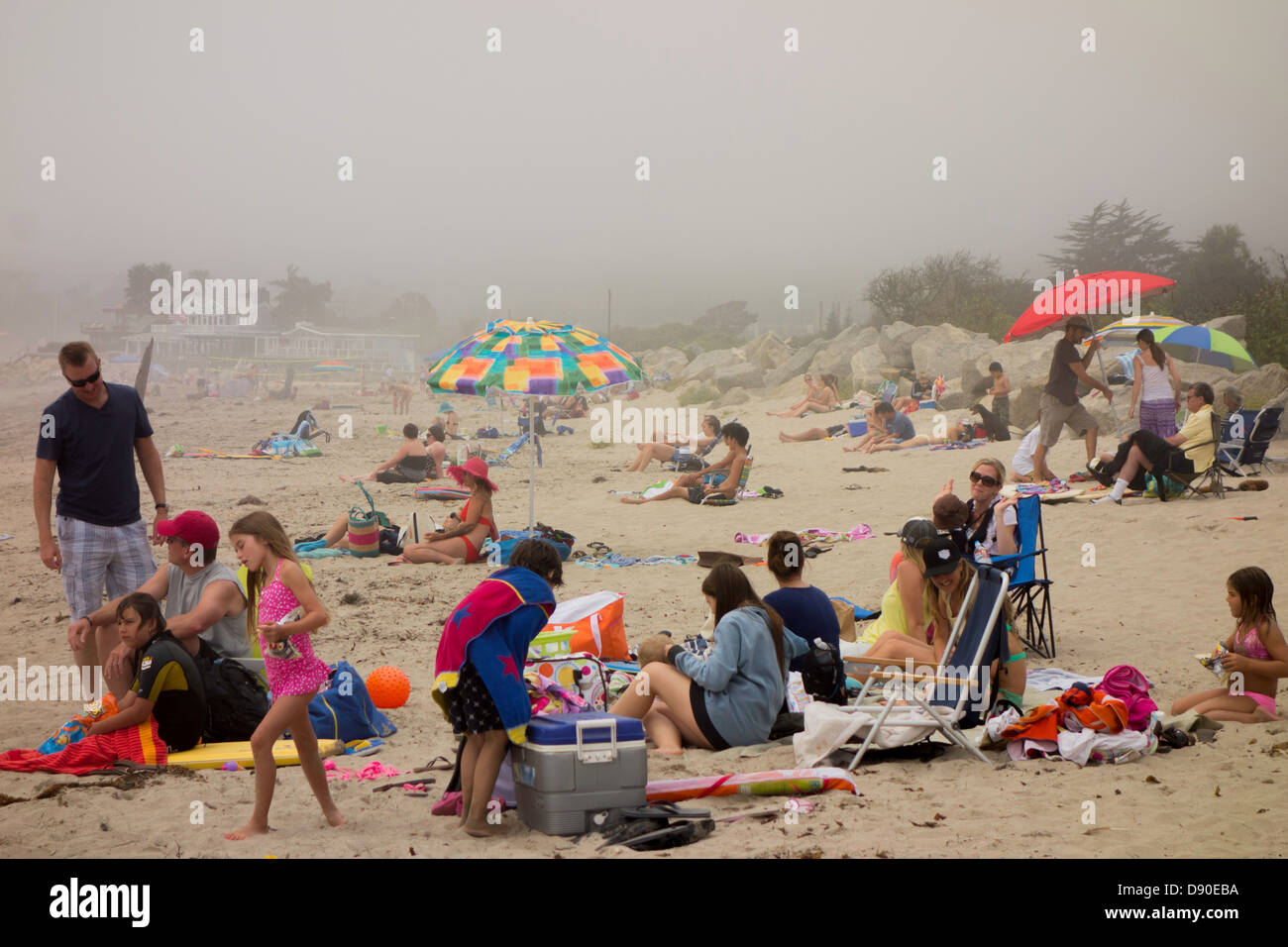 Families on beach on gloomy foggy June day on the coast of California United States - Stock Image