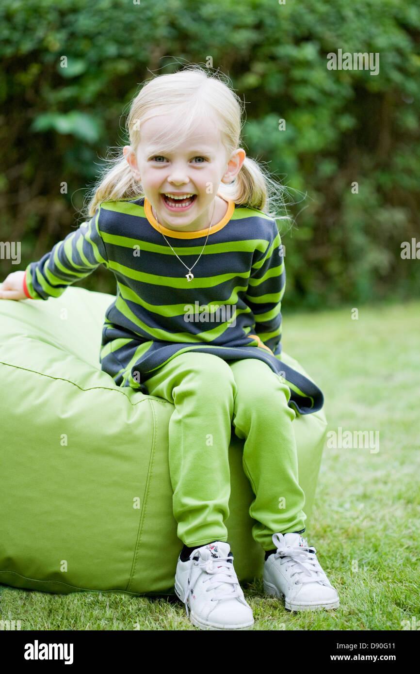 Girl sitting on bean bag on garden - Stock Image