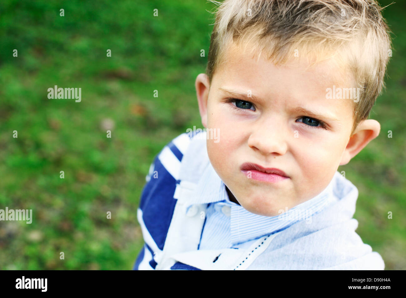 Boy scowling, looking at camera - Stock Image