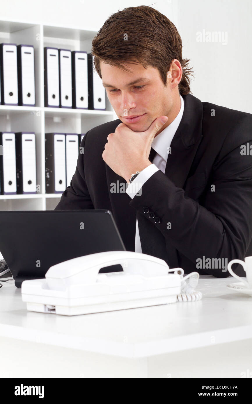 thoughtful or stressful businessman at work - Stock Image