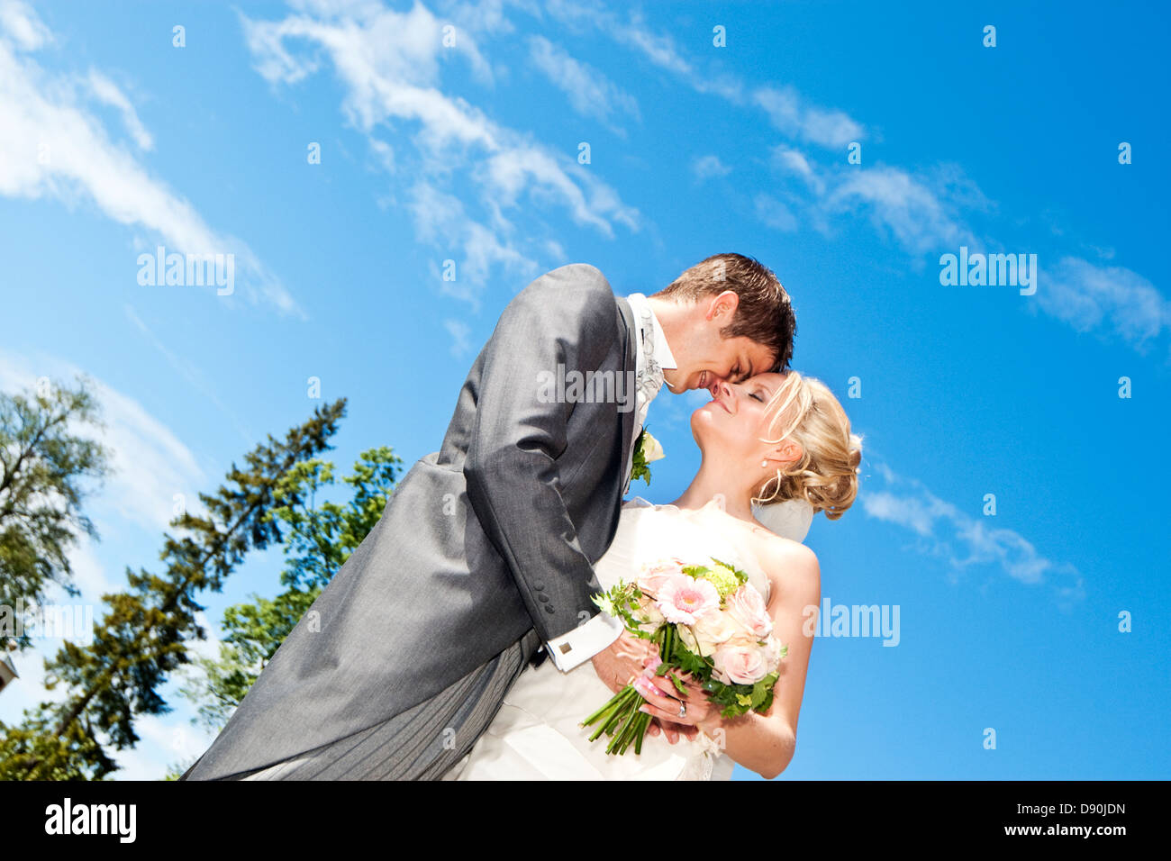 Low-angle view of groom and bride embracing outdoors Stock Photo