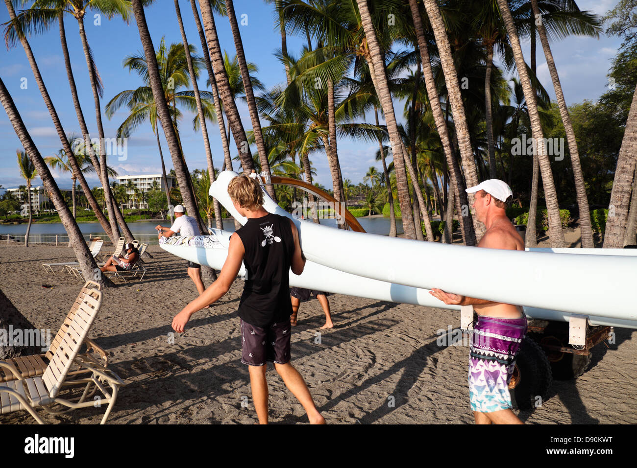 Club members carry outrigger canoe to shoreline at Anaehoomalu Bay in Waikoloa on the Big Island of Hawaii - Stock Image