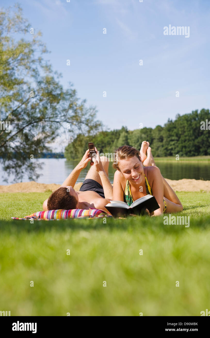 Couple lying on grass, man reading and woman using mobile phone - Stock Image