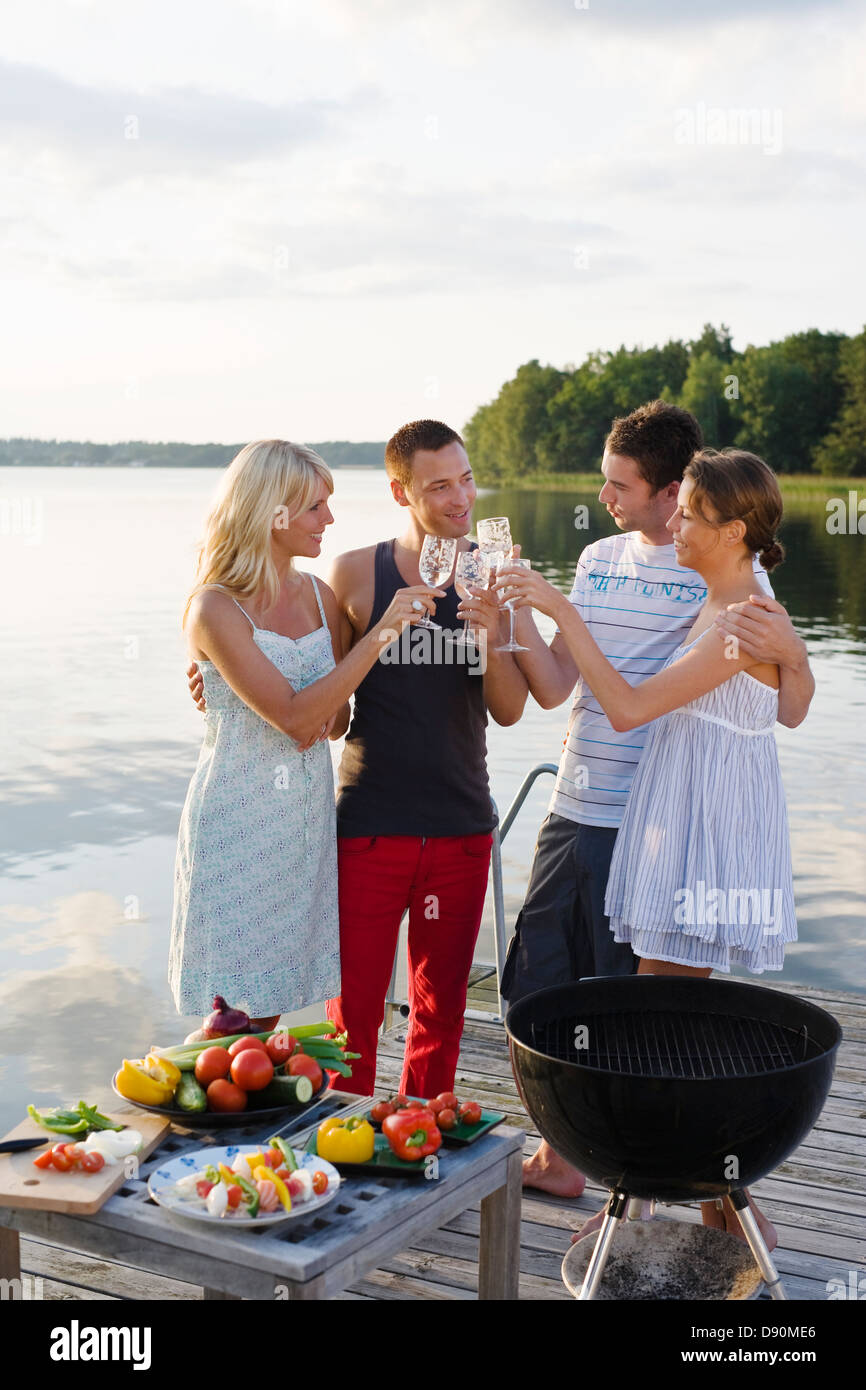Four people standing on jetty and toasting with glasses Stock Photo