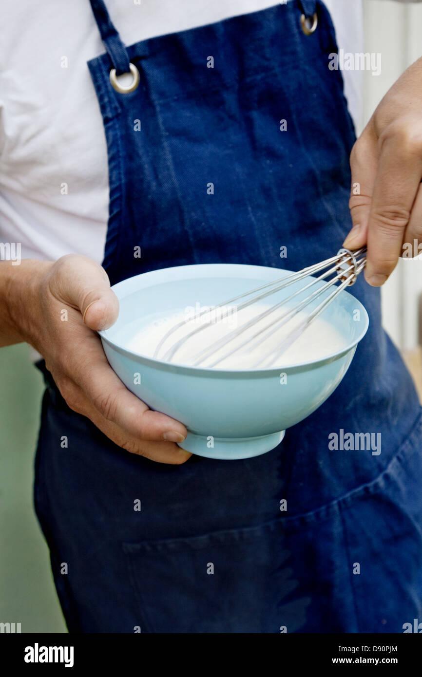 Man whisking in bowl - Stock Image