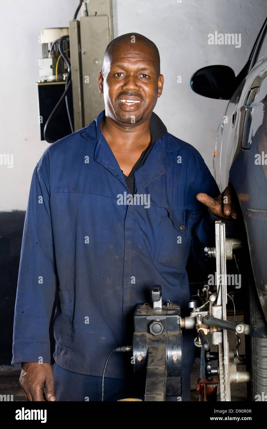 african american auto mechanic working on a vehicle wheel alignment - Stock Image