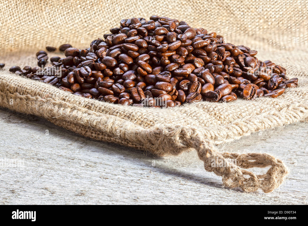 Coffee Beans on Burlap Sack - heap of roasted coffee beans on a burlap or jute sack. - Stock Image