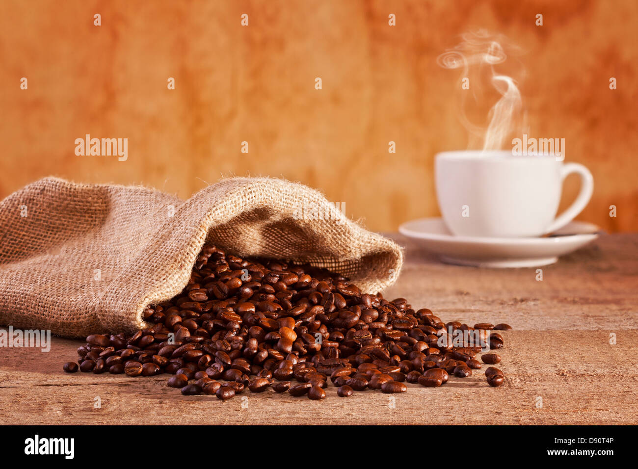 Coffee Beans and Burlap Sack - roasted coffee beans spilling from a burlap sack, cup of coffee with visible steam... - Stock Image