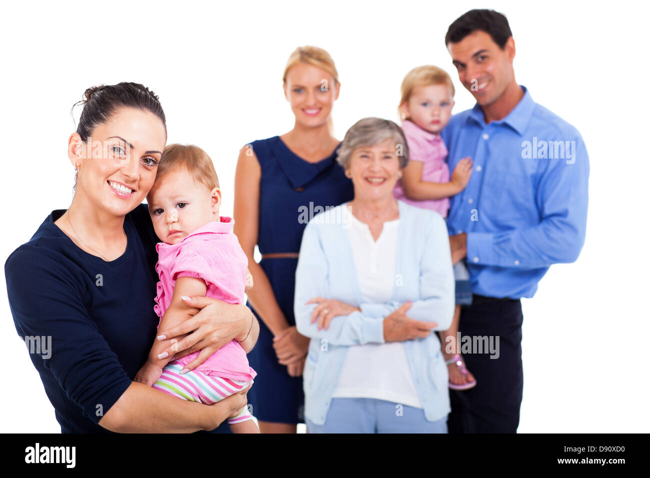 portrait of young woman holding her baby with extended family on background - Stock Image