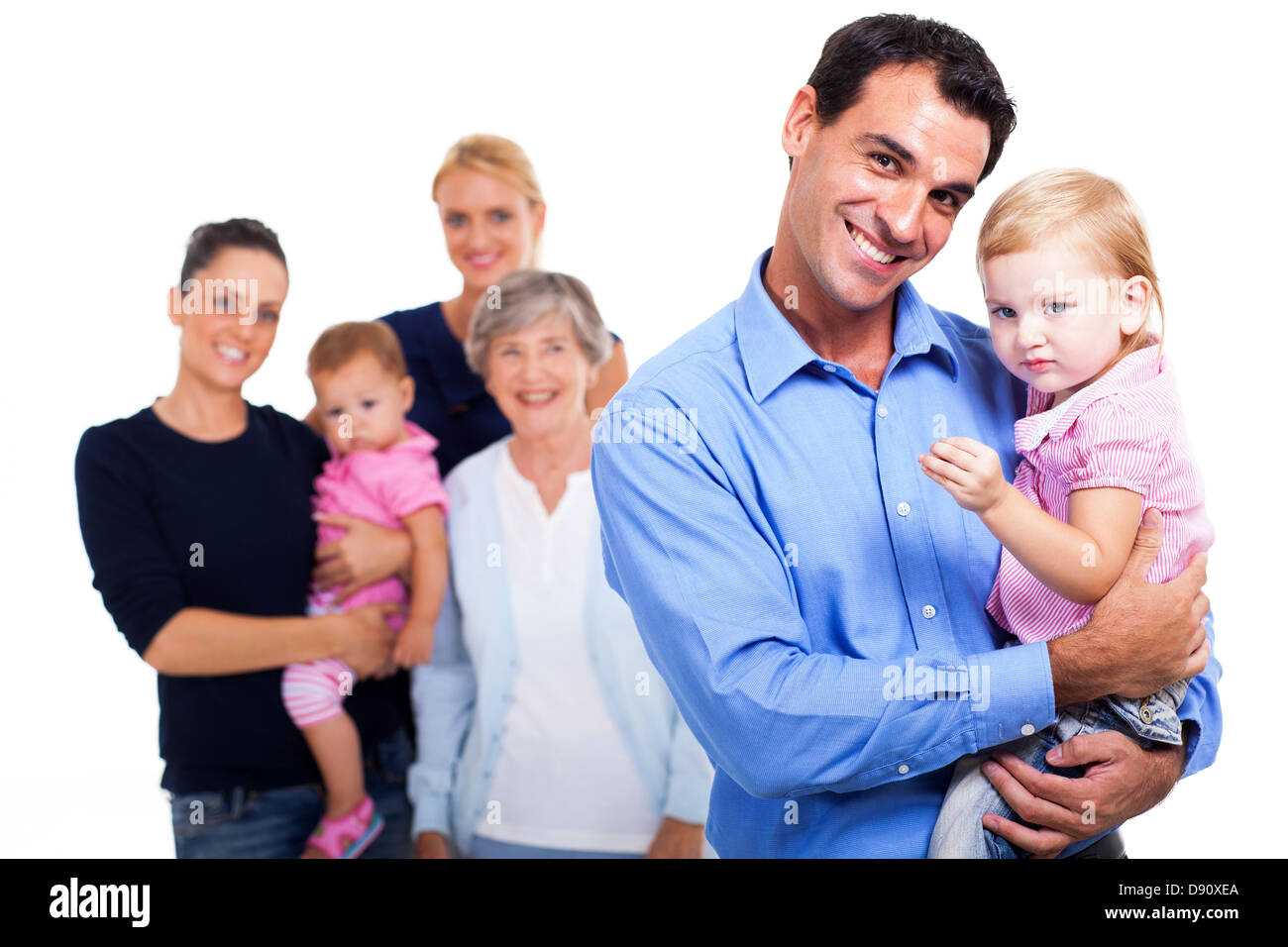 cheerful father holding his daughter with extended family on background - Stock Image