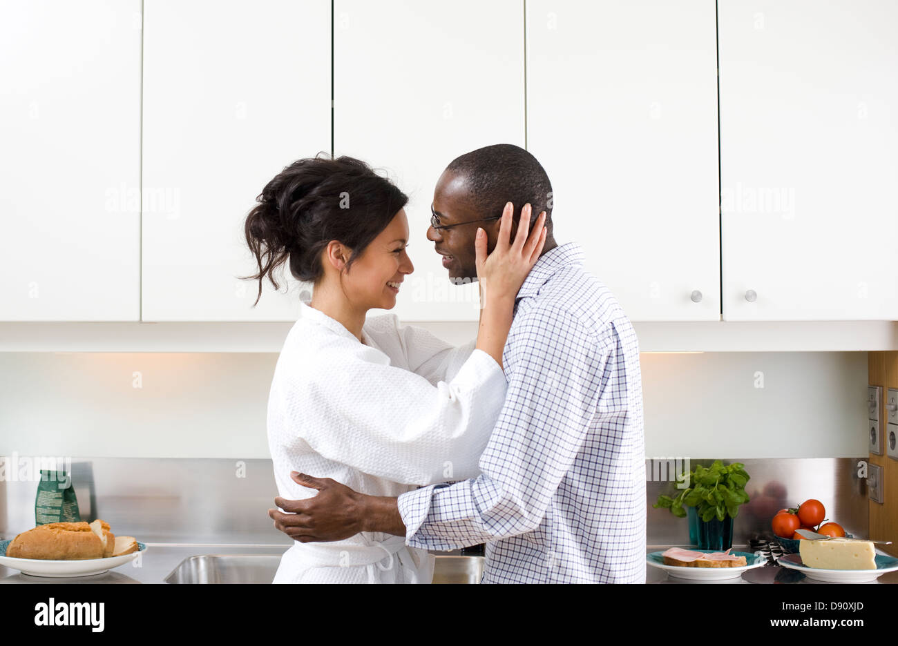 Couple embracing in kitchen in morning - Stock Image