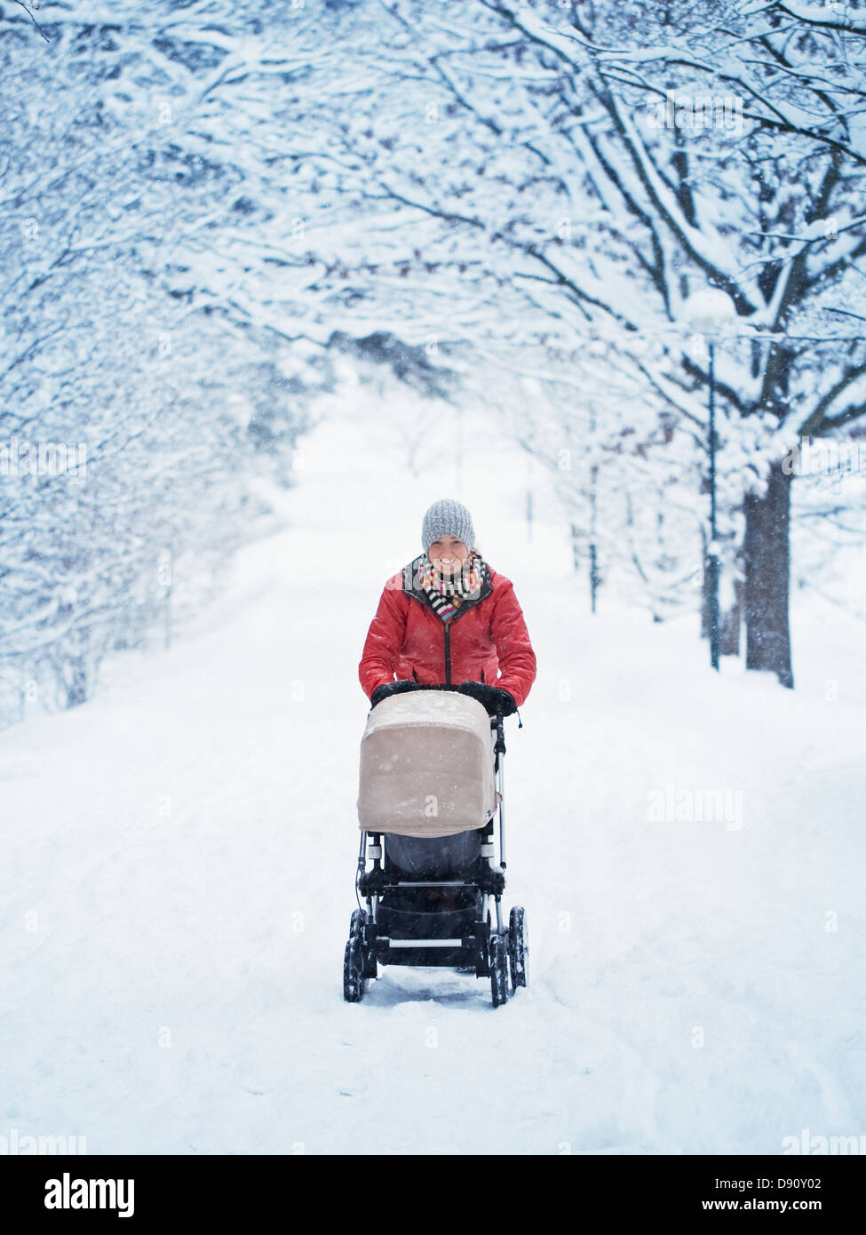 Smiling mother walking with pram at winter landscape - Stock Image