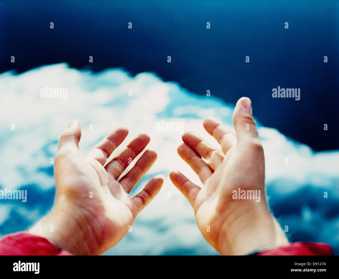 Hands reaching towards the sky. - Stock Image