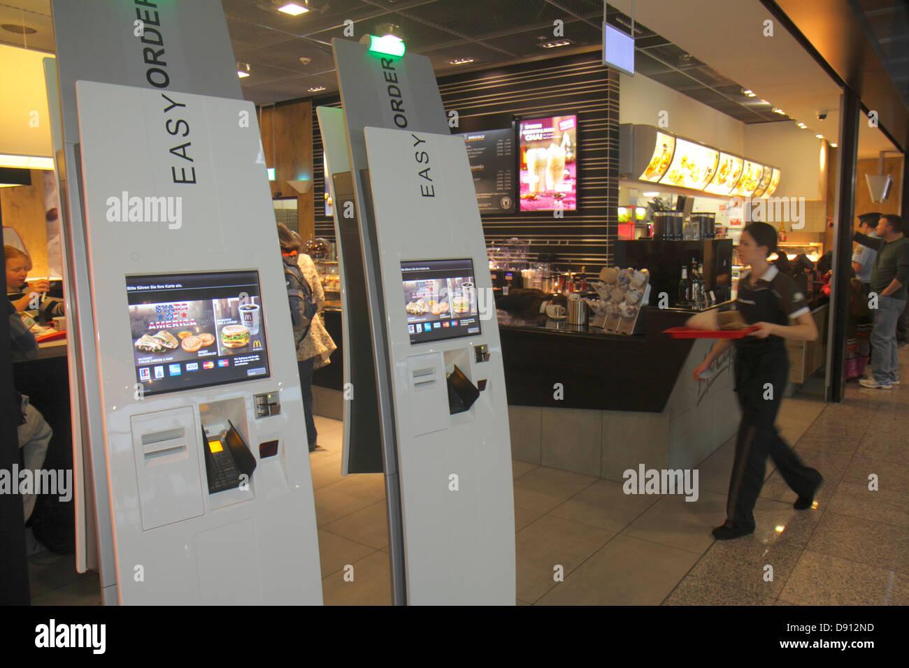 Germany Frankfurt am Main Airport FRA terminal gate area concourse McDonald's fast food restaurant self-service - Stock Image