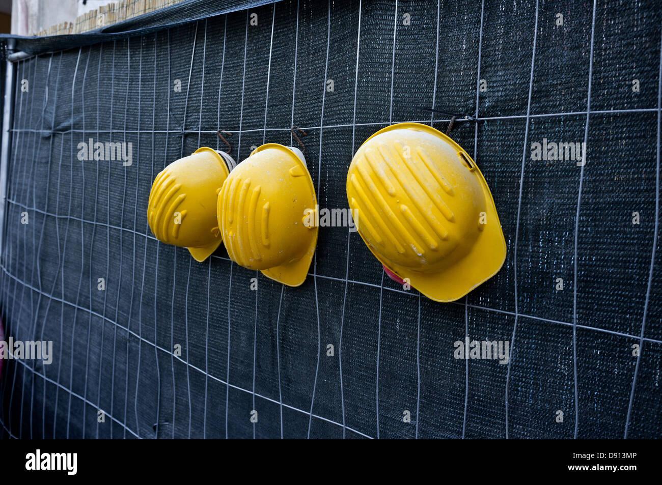 Three yellow hardhats hanging - Stock Image