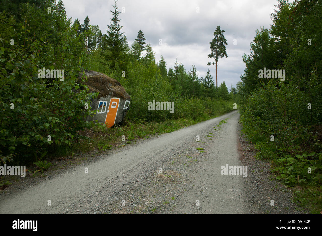House painted on rock along graveled road - Stock Image