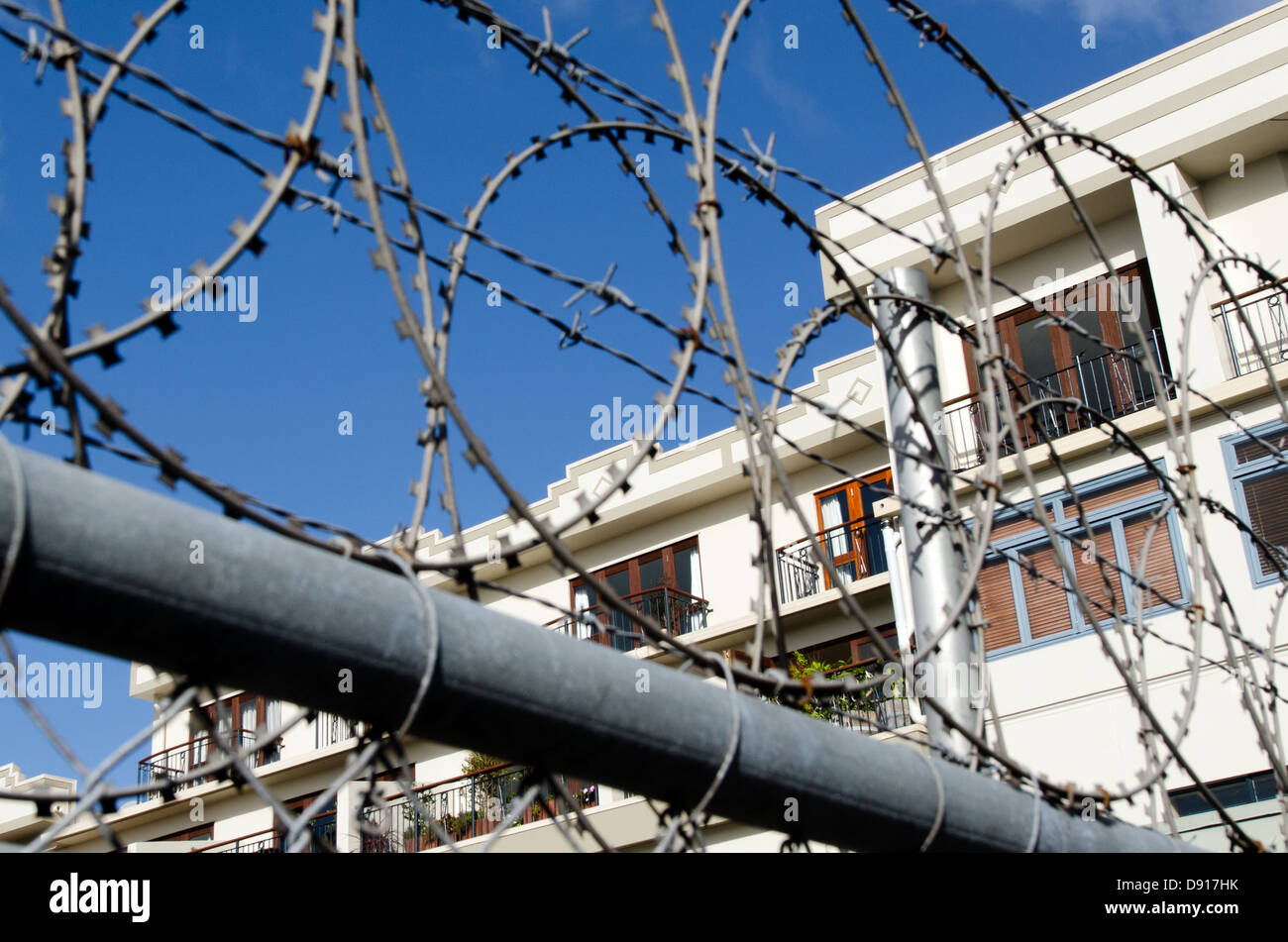 A wealthy, upscale neighborhood community with very rich people behind a protection bar wire fence. - Stock Image