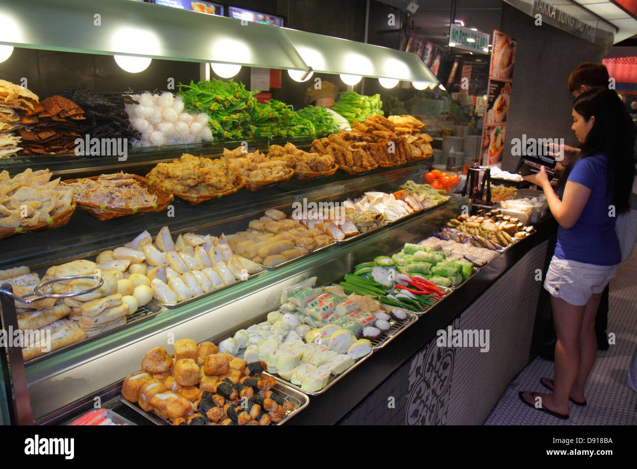 Singapore The Shoppes at Marina Bay Sands shops shopping Asian man restaurant food court cafeteria - Stock Image