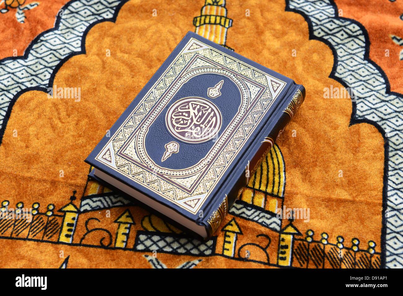 Koran, Quran, Qur'an, Holy Koran book, Quran religious text, Islamic literature Koran on a prayer rug - Stock Image