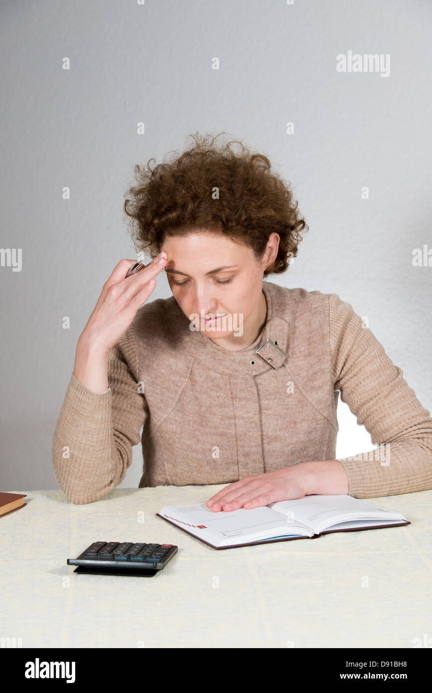 young curly woman works as bookkeeper (accountant) - Stock Image