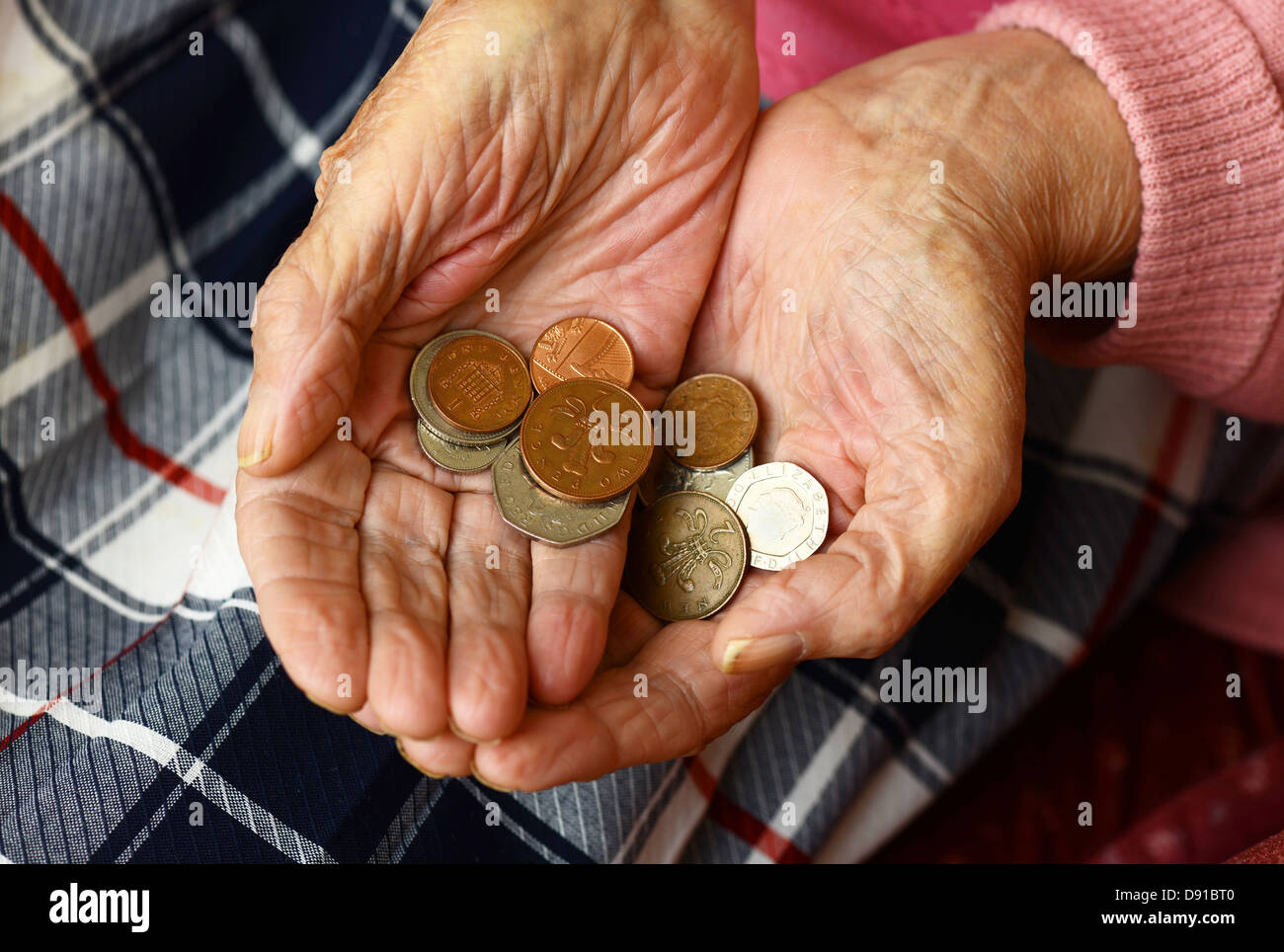 Money, coins in an elderly woman's hands, close up of cash in hands of older woman Stock Photo