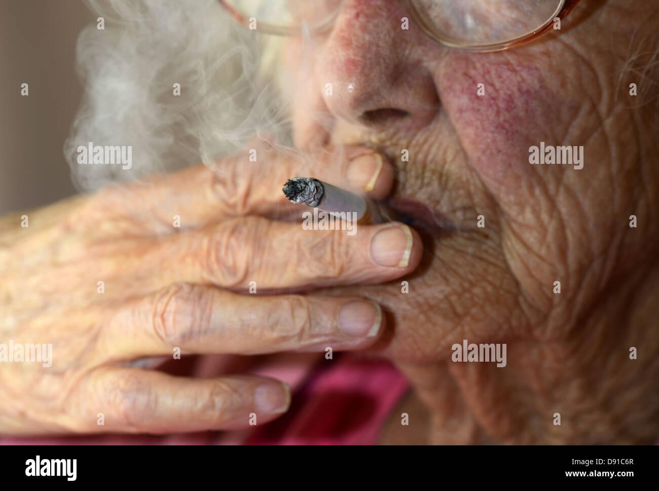 Old woman smoking, elderly woman smoker with a cigarette, elderly lady smoking - Stock Image
