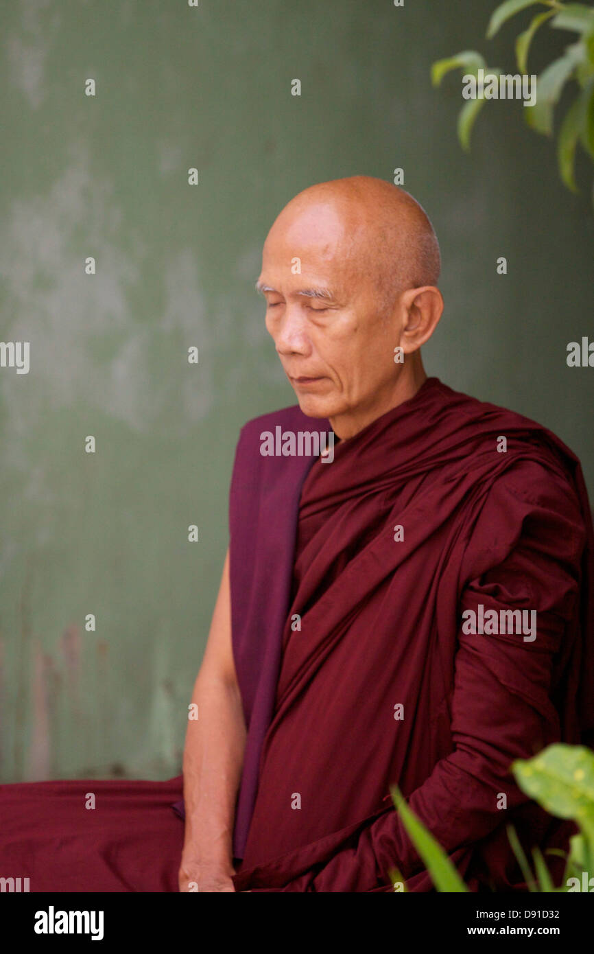 A Burmese Monk Identifiable By His Dark Red Robes Sits In Contemplation Side Alcove