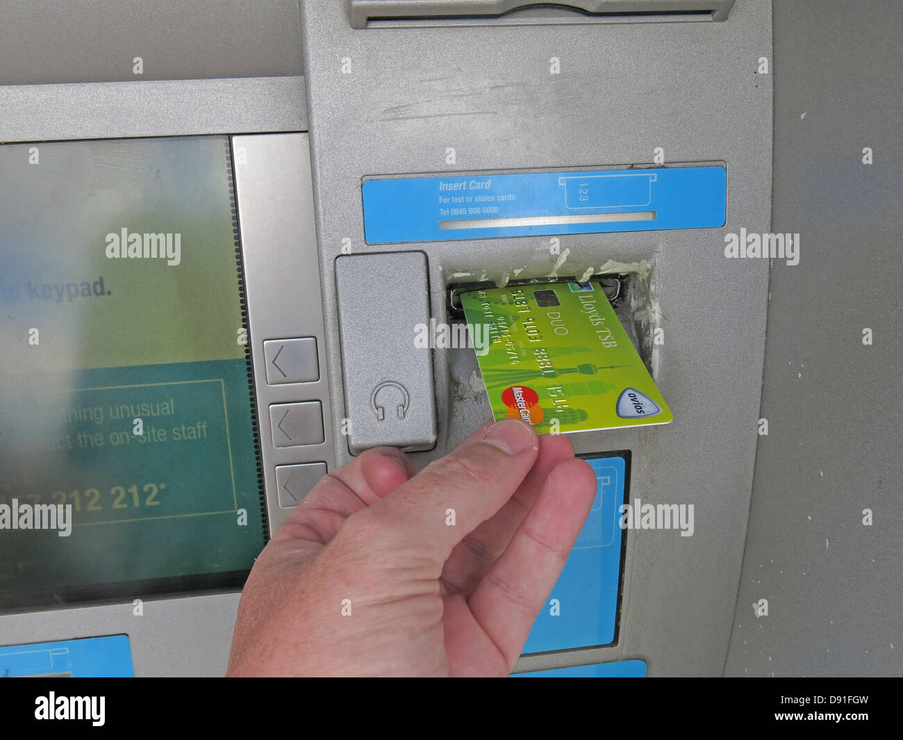 Putting a green Lloyds Avios account card into a co-op cash machine - Stock Image