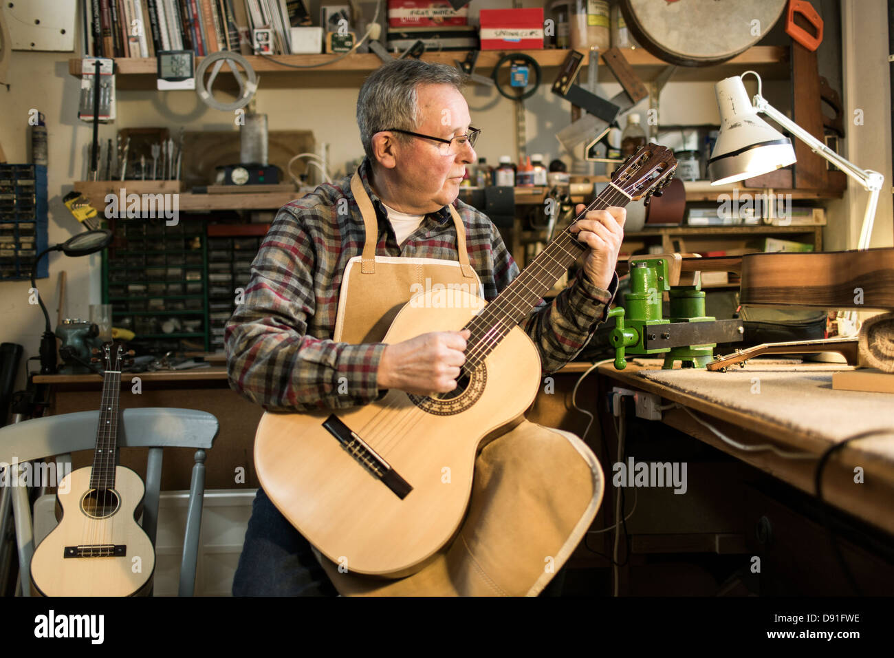 Guitar maker tuning and testing acoustic guitar in workshop - Stock Image