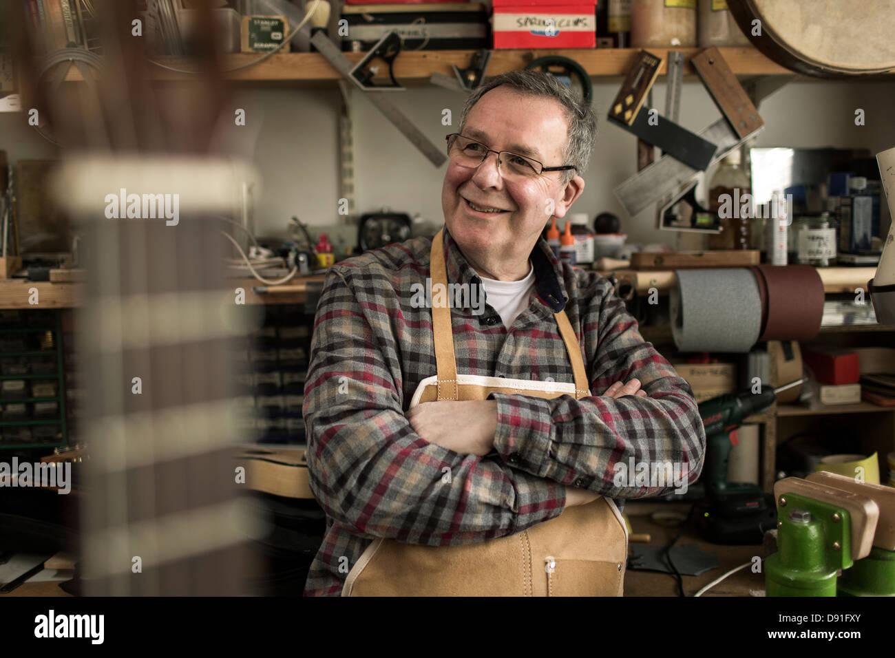 Guitar maker standing in workshop, smiling - Stock Image
