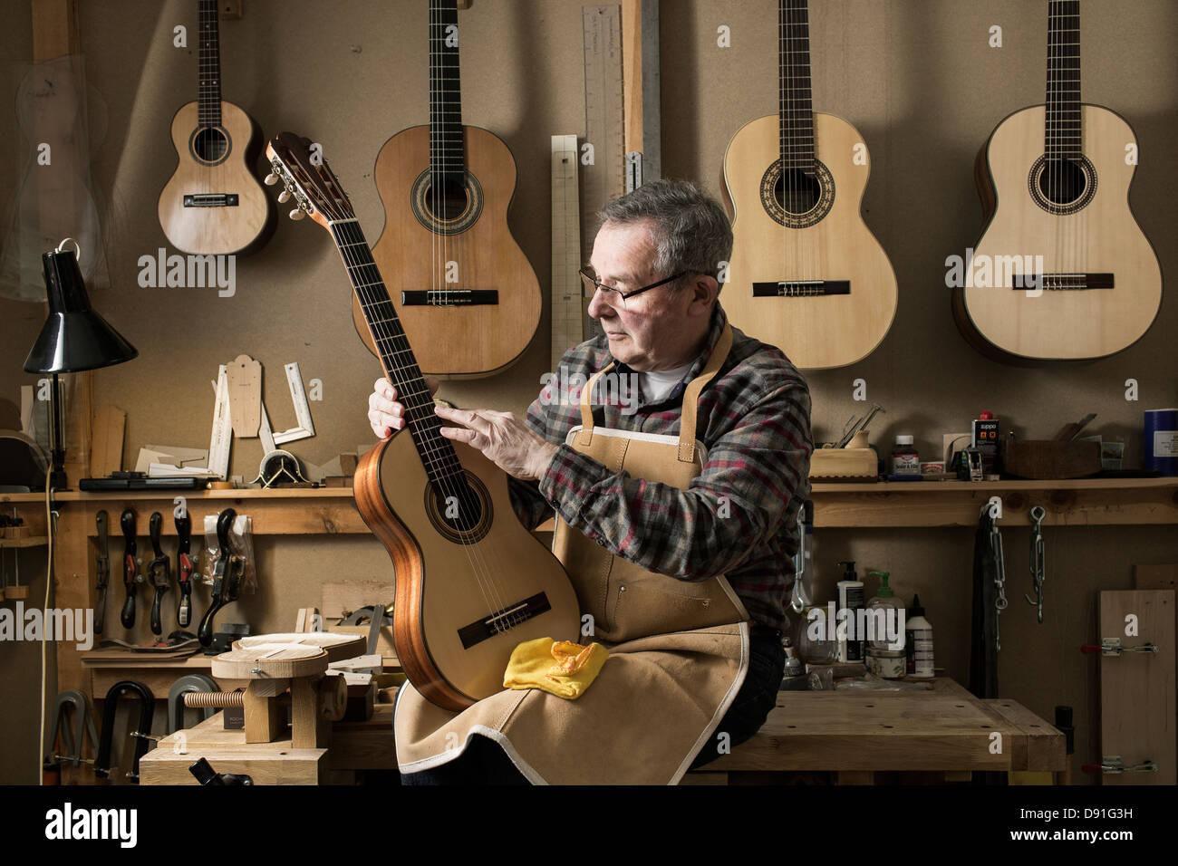 Guitar maker finishing acoustic guitar in workshop - Stock Image